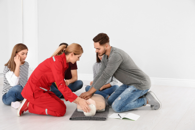 group of people with instructor practicing CPR on mannequin